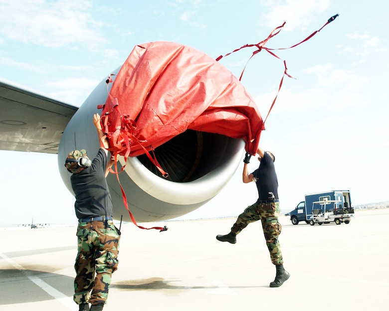 Tech Sgt. David Domagalski and Senior Airman David Reed, 752nd Aircraft Maintenance Squadron, pull a tarp over a KC-135 Stratotanker engine at March Air Reserve Base, Calif., during Patriot Hook 2007. Patriot Hook is a five-day training exercise taking place at three California airfields -- March ARB, North Island and San Clemente Island -- in which military branches come together to practice operational capabilities in a deployed setting.