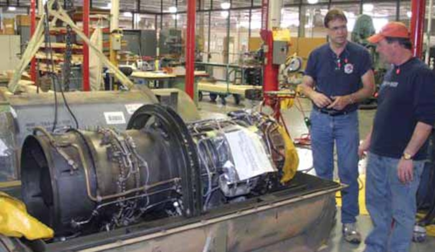Woodworker Howard Holinsworth, left, and packaging specialist T.C. Jones, discuss a special packaging instruction design for a T-64-100 engine. (Courtesy Photo)