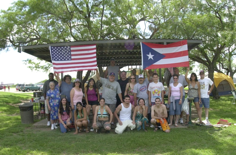 Carlos Santana (located below left hand of Puerto Rican flag), a supply clerk for the Army's  344th Military Intelligence Battalion, is joined by family and friends as he and his wife Trisha (standing to the left) celebrate the Fourth of July for the fourteenth consecutive time at the Goodfellow Recreational Camp at Lake Nasworthy.  