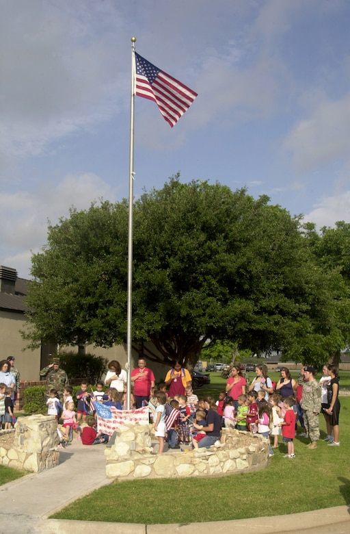 Children, parents and staff from the Child Development Center recite the pledge of allegiance July 3 at the flag pole in front of the Goodfellow NCO Academy. (U.S. Air Force photo by Airman 1st Class Stephen Musal)
