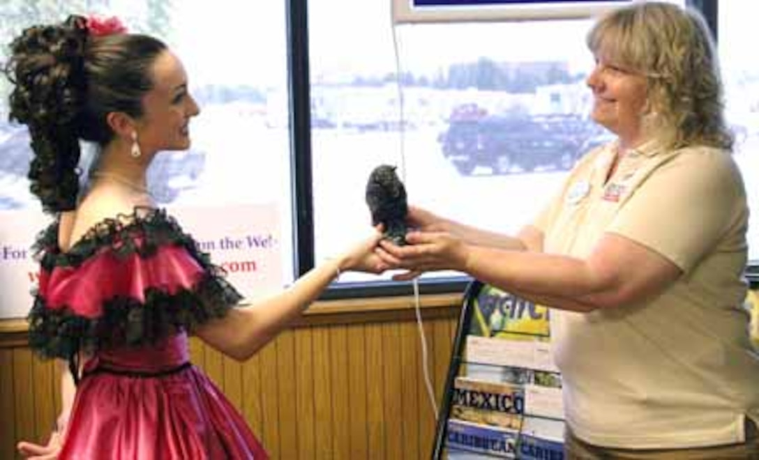 """Heather McKain, a performer at Dolly Parton's Dixie Stampede in Branson, Mo., presents a bronze """"Stampede of the Buffaloes"""" statuette as a token of appreciation to Gabriele Church, Tinker Information, Tickets and Travel director. The award extends a special """"thank you"""" to the ITT office for the services they provide to active duty and retired military personnel and their families. (Air Force photo by Becky Pillifant)"""