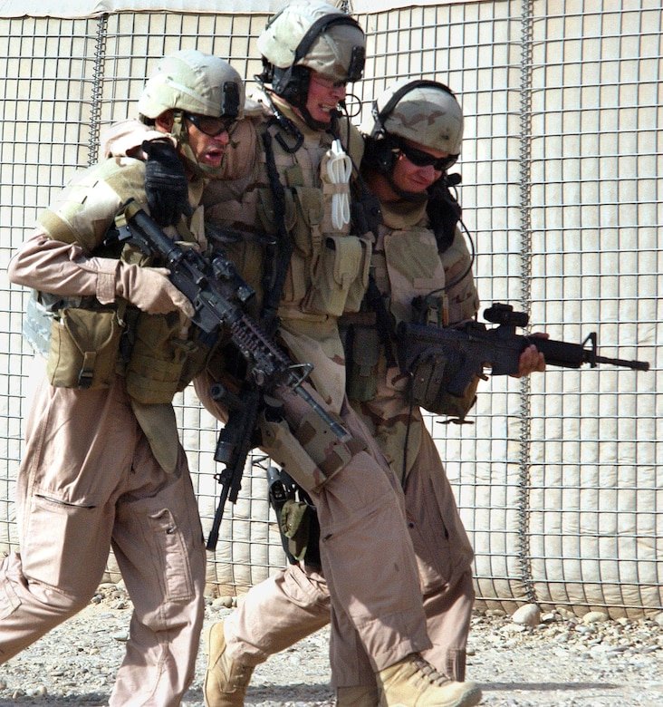 """Master Sgt. Killjan Anderson (left) and Senior Airman John Bretzik, help an """"injured"""" Staff Sgt. Dwayne Pyle back to waiting Humvees during """"battle drills"""" performed before each mission at Contingency Operating Base Speicher, Iraq. All three are members of the 732nd Expeditionary Security Forces Squadron Det. 6 and perform duties as a Provincial Police Transition Team. The drills are designed to simulate any possible situation the team may encounter while conducting missions outside the wire. The PTTs goal is to help the Iraqis establish a functioning, independent police force. (U.S. Air Force photo/Master Sgt. Steve Horton)"""