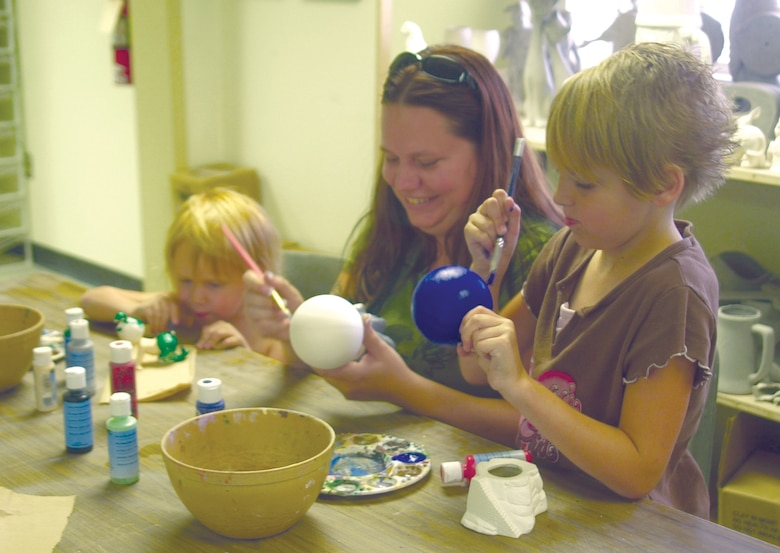 From left to right: Adrienne, Amber and Jasmine Arnold paint a coat of glaze on mold-cast ceramics July 10 at the Arts and Crafts Center. (U.S. Air Force photo by Airman 1st Class Stephen Musal)