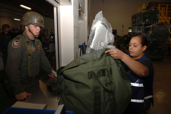 SHAW AIR FORCE BASE, S.C. -- Airman 1st Class Ondina Flores, 20th Communications Squadron base information transfer center custodian, inspects a mobility bag ensuring the proper chemical warfare gear is accounted for before issuing it to Capt. Sean Renbarger, 79th Fighter Squadron F-16CJ pilot, at the Chandler Deployment Processing Center during an Operational Readiness Inspection Aug. 6. The ORI validates the expeditionary skill set of the 20th FW. (U.S. Air Force photo/Staff Sgt. Nathan Bevier)