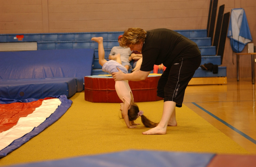 Averi Martin performs a handstand with a little help from gymnastics instructor, Josie Wilkes. (U.S. Air Force photo be Joe Strouth)
