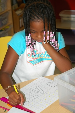 Jazmine Bell, Tyndall Elementary School fourth-grade student, takes a moment to creatively draw her name at the Youth Center's summer program where she spends her days before school starts Aug. 20. (U.S. Air Force photo by Staff Sgt. Vesta Anderson)