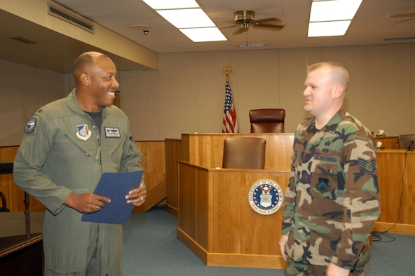 """KUNSAN AIR BASE, Republic of Korea -- Col. CQ """"Wolf"""" Brown, 8th Fighter Wing commander, congratulates Staff Sgt. Phillip Brooks, 8th Fighter Wing Legal Office paralegal, Aug. 1 here. Sergeant Brooks was recognized as the 8th FW's Pride of the Pack for the week of Aug. 1. (U.S. Air Force photo/Staff Sgt. Alice Moore)"""