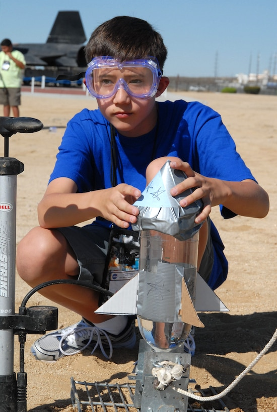 Kenton Hoshino, an 11-year-old camp participant, prepares his bottle rocket made of household items during the rocket launch activity at the NASA Dryden bottle rocket launch pad Aug. 3. The rocket launch was just one of many activities the campers participated in throughout the week. (Photo by Airman 1st Class Mike Young)