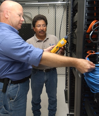 Mr. Rollman, left, and Carlos Iruegas, general manager for Empire Integrated Services of San Antonio, evaluate test results of new station cables inside Hewes Hall.  (U.S. Air Force photo by Kemberly Groue)