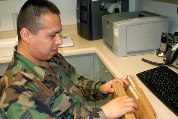 Airman Alarcon reviews genetics test folders.  (U.S. Air Force photo by Steve Pivnick)