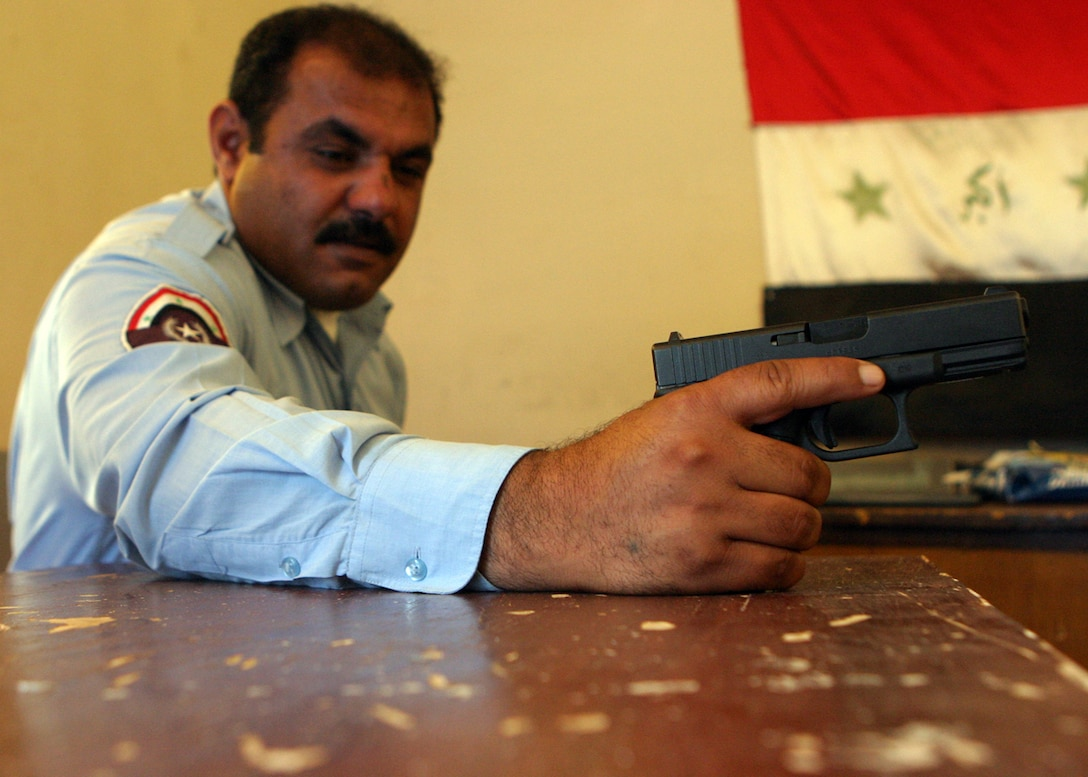 AL QA?IM DISTRICT HEADQUARTERS POLICE STATION, AL QA?IM, Iraq ? An Iraqi policeman, or IP, with the Al Qa?im district police proudly holds his pistol while the Iraqi flag hangs in the background.  The police here have grown up with the townspeople thus creating a close bond with one another.