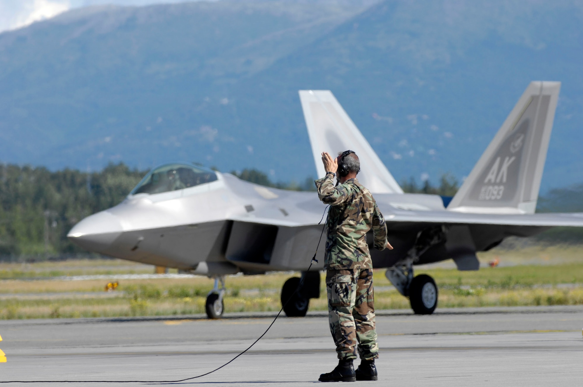 A crew chief marshals an F-22 Raptor into place at Elmendorf Air Force Base, Alaska, during a ceremony marking the aircraft's arrival Aug. 8. Six F-22s took part in the ceremony, with the base scheduled to receive 34 additional aircraft. Elmendorf should have its full complement of 40 aircraft by December 2009. (U.S. Air Force photo/Tech. Sgt. Keith Brown)