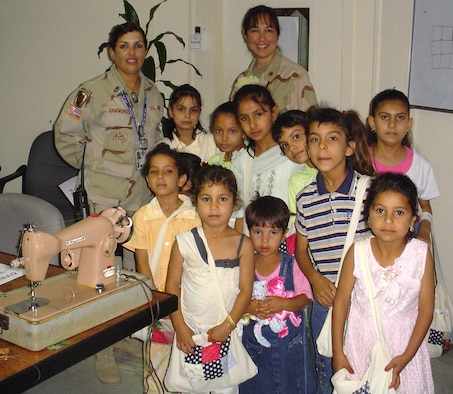 Lt. Col. Linda K. Bethke (right), 11th Contracting Squadron commander, and Army Sergeant 1st Class Maggie Hammonds pose with a group of Iraqi children they taught to quilt. (Courtesy photo)