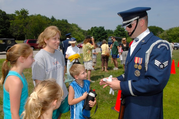 HANSCOM AFB, Mass. -- Air Force Honor Guard Drill Team member Senior Airman James Cashwell chats with Brenda Huff, wife of Capt. Richard Huff, and their children Rebecca, 11, Sarah, 7, and Jake, 6, following a Drill Team performance in Minute Man National Historical Park in Lexington, Mass. Aug. 7. The Huff family recently relocated to Hanscom. The Drill Team conducted two performances during their visit to the base. On Aug. 6 the Drill Team performed on base for the base populace; on Aug. 7 the Drill Team performed for the public in the park. (U.S. Air Force photo by Jan Abate)