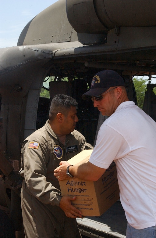 Navy Chaplain (Lt.) Dennis Wheeler, right, from the USS Pearl Harbor hands Army Sgt. First Class Julio Ascencio, a crew chief with the 1st Battalion 228th Aviation Regiment at Soto Cano Air Base, Honduras a box of humanitarian supplies to load into a UH-60 Black Hawk. The supplies were transported to villiages in southern Honduras as part of Project Handclasp, a partnership between the Navy and corporations, public service organizations, non-government organizations and individuals throughout the United States to provide humanitarian assistance overseas. Members of Joint Task Force-Bravo assisted the Navy with logisitics, ground and air support. Air Force photo by Senior Airman Shaun Emery.