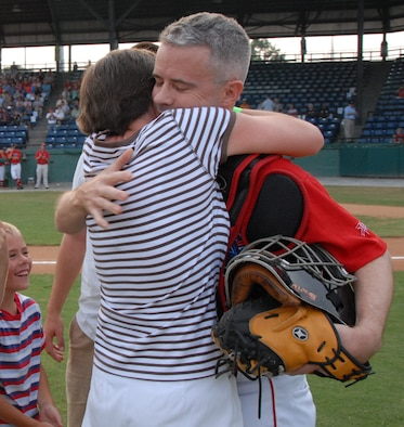 Lt. Col. Mark Wade hugs his wife Joan during opening ceremonies of the Macon Music game Monday night. Col Wade, who has been deployed for six months surprised his family after being disguised as a Macon Music catcher. U. S. Air Force photo by Sue Sapp
