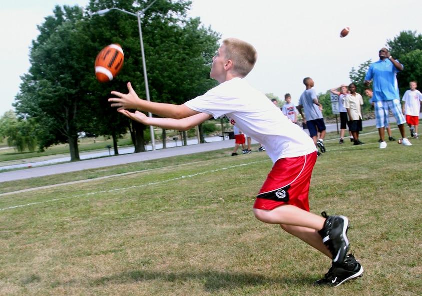 WHITEMAN AIR FORCE BASE, Mo. - Ryan Burk, son of Michelle and Tech. Sgt. Randy Burk, 509th Operations Support Squadron, receives a pass from Neil Smith Aug. 8 during a youth football clinic at the base soccer field. Neil Smith helped teach children the fundamentals of football during the clinic. He is currently a co-owner of the Kansas City Brigade and has played as a defensive lineman for the Kansas City Chiefs, the Denver Broncos and the San Diego Chargers. He has won two National Football League championship rings for Super Bowls XXXII and XXXIII. (U.S. Air Force photo/Airman 1st Class Stephen Linch)