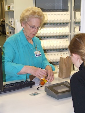 Lorraine Robertson, one of the 62nd Medical Group's volunteers, helps a customer get her prescription filled at the clinic's pharmacy.