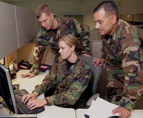 "Capt. John McInnis, ""A"" flight chief; and manpower analysts Staff Sgt. Emily Johanneck and Tech. Sgt. Ed Tafolla, compile statistics for a manpower study in the 5th Manpower Requirements Squadron.  Housed in Bldg. 210 West, the organization is a tenant that helps the Air Force determine manning needs."