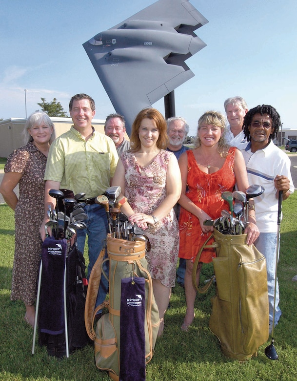 B-2 personnel rallied after learning a coworker's deployed husband and other Airmen shared one broken golf club during down time.  Angela Carr, center, is surrounded by coworkers and a few of the golf supplies going overseas.  From left are; Diane Elliott, Kirk Johnson, Tommy Mills, Charlie Hogan, Tina Croswell, Randy Lynn and Gary Kinard.  (Air Force photo by Margo Wright)
