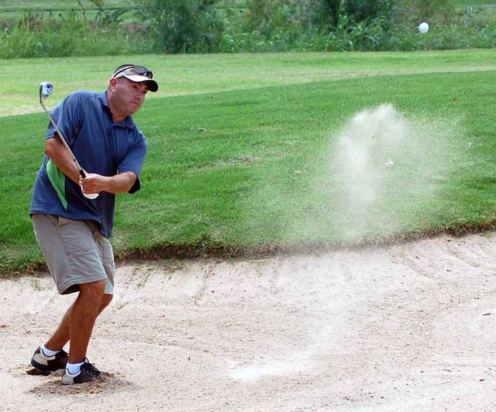 552nd Operational Support Squadron golfer Rick Villarreal chips a bunker shot during the back nine of the small squadron golf championship held Aug. 2 at the Tinker Golf Course. (Air Force photo by John E. Banks)