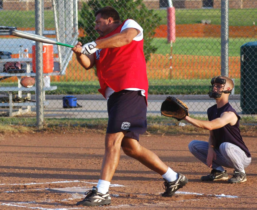 Tinker Fire Department catcher Tom Trella drives the ball out of the infield during a game against the 34th Combat Communications Squadron. (Air Force photo by John E. Banks)