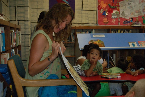 """ANDERSEN AIR FORCE BASE, Guam - Emilie Fidler, a library aide for the 36th Services Squadron, reads """"The Wind Blew"""" by Pat Hutchins to children attending Story Time at the base library July 25.  Story Time is held every Wednesday at 10:30 a.m. and at 3 p.m.  The activity is designed to encourage children to participate in reading.  (U.S. Air Force photo by Airman 1st Class Carissa Morgan/ 36th Wing Public Affairs)"""