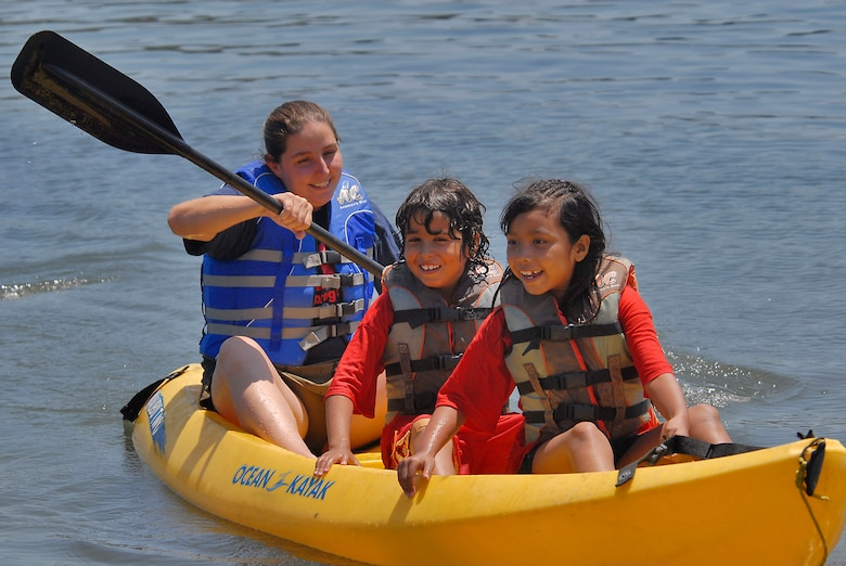 Three youth summer campers paddle a kayak on the Pacific Ocean. More than 38 children in the Youth Summer Camp Program spent the day kayaking, picnicking, and playing in the sand at Mothers' Beach in Long Beach, Aug. 8.  (Photo by Joe Juarez)