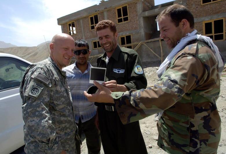 Panjshir Provincial Reconstruction Team commander Lt. Col. Christopher Luedtke (left) and Anaba district police chief Zardot Towhidi (center) share a laugh over some photos they took Aug. 6 during a training session. Colonel Luedtke brought members of his PRT to the Anaba district of Panjshir province, Afghanistan, to provide training to Afghan National Police serving in the area. Colonel Luedtke is deployed from Hill Air Force Base, Utah. (U.S. Air Force photo/Master Sgt. Jim Varhegyi)