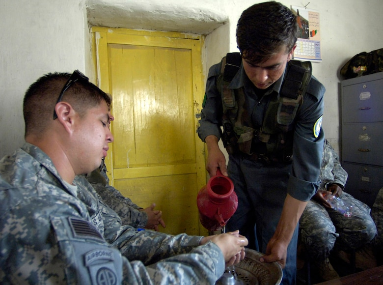 Panjshir Provincial Reconstruction Team member Staff Sgt. Andre Sanchez-Romero gets his hands rinsed off by a member of the Afghan National Police before enjoying a traditional meal of nan (bread), rice, roasted meat, fresh vegetables and chai tea provided by Anaba district police chief Zardot Towhidi Aug. 6. Sergeant Sanchez-Romero is deployed from Minot Air Force Base, N.D. (U.S. Air Force photo/Master Sgt. Jim Varhegyi)