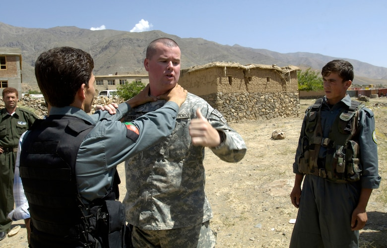 Tech. Sgt. Michael Downey demonstrates how to escape from a choke hold to members of the Afghan National Police Aug. 6.  The security forces Airman, a member of the Panjshir Provincial Reconstruction Team, traveled with other PRT members to the Anaba district of Panjshir Province, Afghanistan, to provide training to ANP working in the district. Sergeant Downey is deployed from the Pentagon, Washington, D.C.  (U.S. Air Force photo/Master Sgt. Jim Varhegyi)