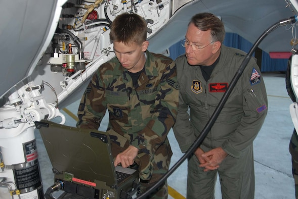 Senior Airman Temujin Ching, 477th Maintenance Squadron crew chief, shows Lt. Gen. John A. Bradley, Air Force Reserve Command commander, some of the new technology used on the F-22 Raptor. (Air Force photo by Master Sgt. Chance C. Babin)