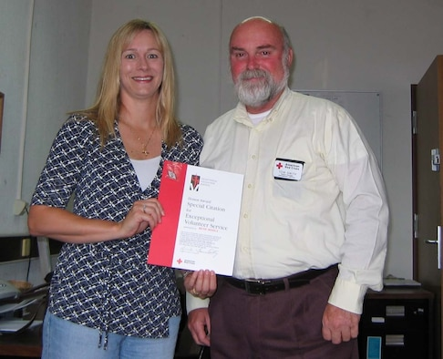 SPANGDAHLEM AIR BASE, Germany -- Rene Hohls receives an American Red Cross Exceptional Volunteer Award from Tom Smith, Red Cross station manager, for her outstanding work within the Spangdahlem Air Base community during the past two years. Mrs. Hohls served as the Schools Chair human resource chair and participated in multiple community activities while representing the Red Cross. Mrs. Hohls is the Level 1 winner of the Armed Forces Emergency Services Award for her assistance to the Spangdahlem Elementary School which was selected for the Laura Bush Foundation for America's Libraries award of $5,000. Mrs. Hohls's award package will be forwarded to the Level II competition. (Courtesy photo)