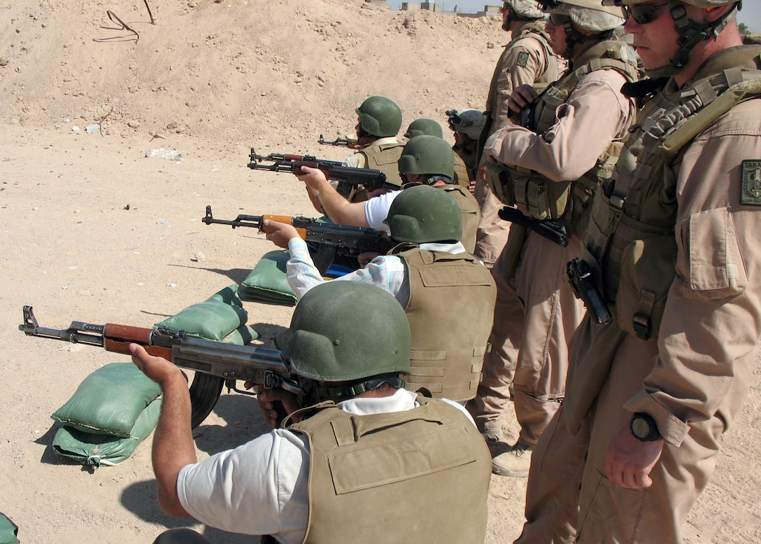CAMP GANNON, HUSAYBAH, Iraq ? Marines with Viking Red Section, Mobile Assault Platoon, Regimental Combat Team 2, observe an Iraqi personal security detachment fire AK-47 rifles on a firing range here.  The Iraqis are training to be a personal security detachment for the judges in the area.