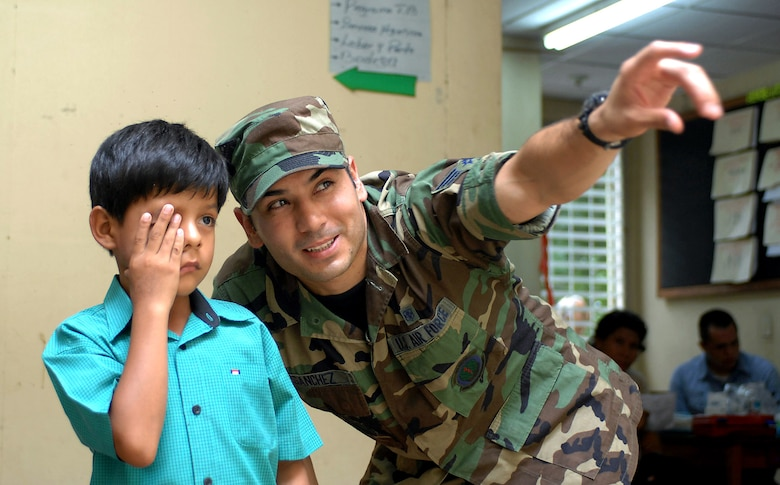 Airman Sebastian Sanchez assists a child during an eye examination July 21 at the 15 de Julio Health Care Center in Chinandega, Nicaragua. The USNS Comfort is on a four-month humanitarian deployment to Latin America and the Caribbean providing medical treatment to patients in a dozen countries. Airman Sanchez is a laboratory technician attached to the Military Sealift Command hospital ship USNS Comfort. (U.S. Navy photo/Petty Officer 2nd Class Steven King)