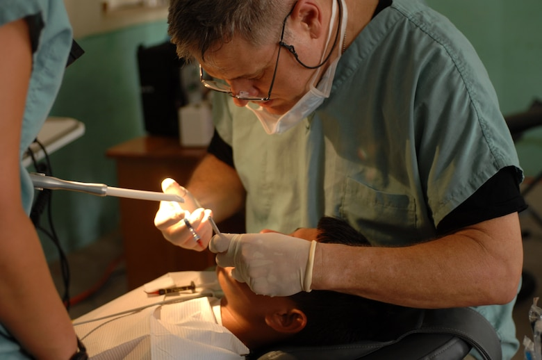 Lt. Col. (Dr.) Richard Tate provides dental care for a patient as Staff Sgt. Monica Christman helps Aug. 1 at the San Pablo Roman Catholic School in San Pablo, Belize. The U.S. Military Sealift Command hospital ship USNS Comfort is on a four-month humanitarian deployment to Latin America and the Caribbean providing medical treatment to approximately 85,000 patients in a dozen countries. While deployed, USNS Comfort is under operational control of U.S. Naval Forces Southern Command and tactical control of Destroyer Squadron 24. Colonel Tate is a deployed Air Force dentist and Sergeant Christman is a dental assistant. (U.S. Navy photo/Petty Officer 2nd Class Elizabeth Allen)