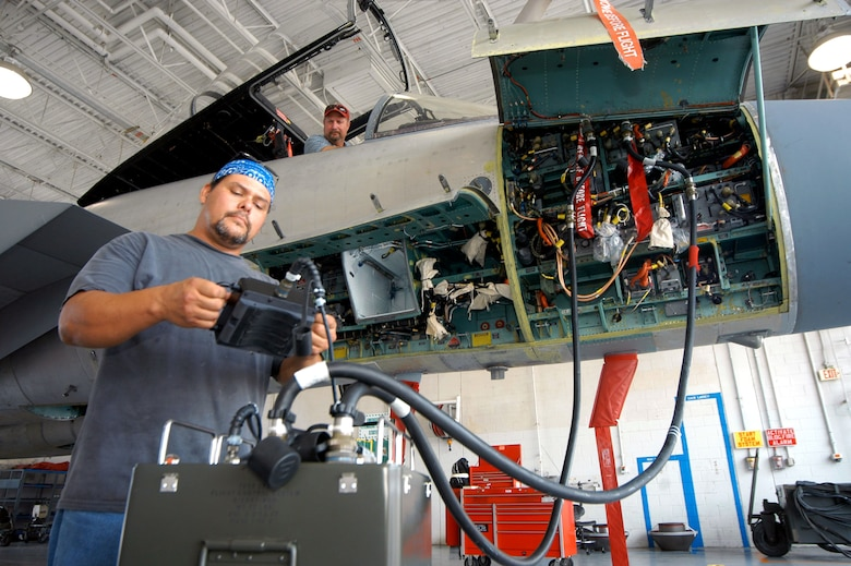John Hysell and Henry Sparks get a look at one of the automated flight test control systems of an F-15 Eagle during a demonstration Aug 1 at Robins Air Force Base, Ga. The tester plugs into the F-15, like hooking up a car engine to a computer to discover engine trouble. Mr Hysell and Mr. Sparks are aircraft mechanics. (U.S. Air Force photo/Sue Sapp)