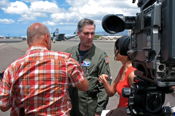 "Lt. Col. Kurt Nelson talks with reporters Aug. 13 on the flightline at Hickam Air Force Base, Hawaii. Colonel Nelson is an airborne reconaissance weather officer with the 53rd Weather Reconnaissance Squadron out of Keesler Air Force Base, Miss. He and and several other ""Hurricane Hunters"" are flying C-130 Hercules weather reconnaissance missions out of Hickam AFB, Hawaii, to track Hurricane Flossie, a Category 4 storm moving toward Hawaii. (U.S. Air Force photo/Tech. Sgt. Chris Vadnais)"