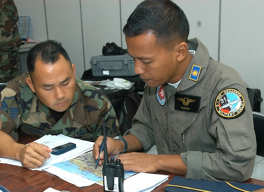 Master Sgt. Joe Howell, 353rd Special Operations Group air space controller, goes over control tower issues with Capt. Edwardus Wisoko, operations chief for Squadron 31 of the Indonesian Air Force.  The exchange was part of Exercise Teak Iron, an exercise between the U.S. Air Force and the Indonesian Air Force.
