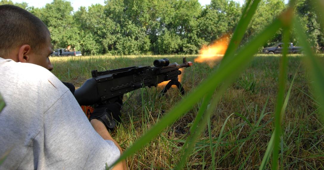 An insurgent acted out by Airman 1st Class Chance Farmer, 509th Security Forces Squadron, fires his M249 Squad Automatic Weapon at a convoy of Airmen at the Cobra Site during Air Expeditionary Combat Skills training Aug 10. (U.S. Air Force photo/Airman 1st Class Stephen Linch)