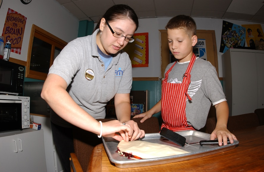 EIELSON AIR FORCE BASE, Alaska -- (Left) Ms. Stephanie Cox, Youth Center staff, helps Kaleb Albert, son of Heather and Staff Sgt. Matthew Albert, 354th Contracting Squadron, fold over the pastry desert to place in the oven August 14 at the Youth Center. The Youth Center is conducting a six-week cooking program for children aged 9-12 to teach them the importance of eating healthy and experimenting with different tastes.  (U.S. Air Force Photo by Airman 1st Class Jonathan Snyder)(Released)
