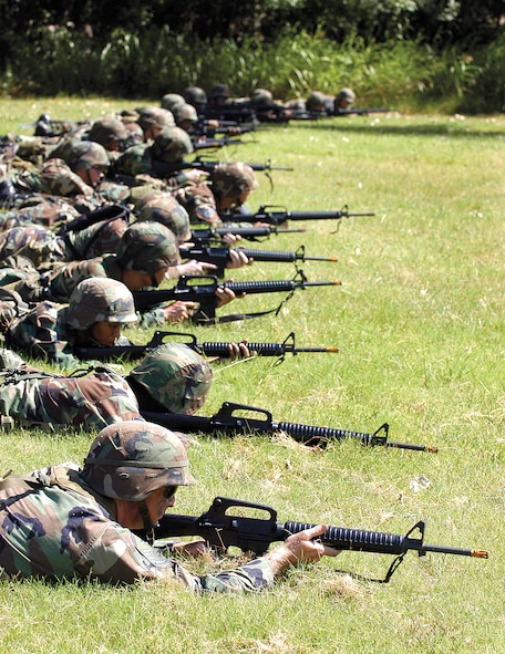 """Airman practice tactical movements as Tinker AFB, Okla. Combat Readiness School instructors bark directions. Twenty-five pounds of gear and pounding sun require frequent hydration and have students finding ways to battle eye-stinging sweat. """"If you get yourself a '70s (John) McEnroe headband, I'll make you do push ups forever!"""" warns school commandant Master Sgt. Brian Kaut. (U.S. Air Force photo by Margo Wright)"""