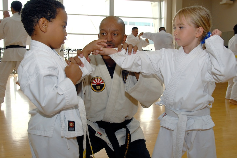 Alonzo M. Jones instructs Quentin Evans, 4, and Avianna Raupach, 6, in the Cory Jitsu / Comba-tai discipline. Martial Arts students and fans gathered at the Los Angeles AFB Fitness Center for a demo, Aug. 11.  (Photo by Joe Juarez)