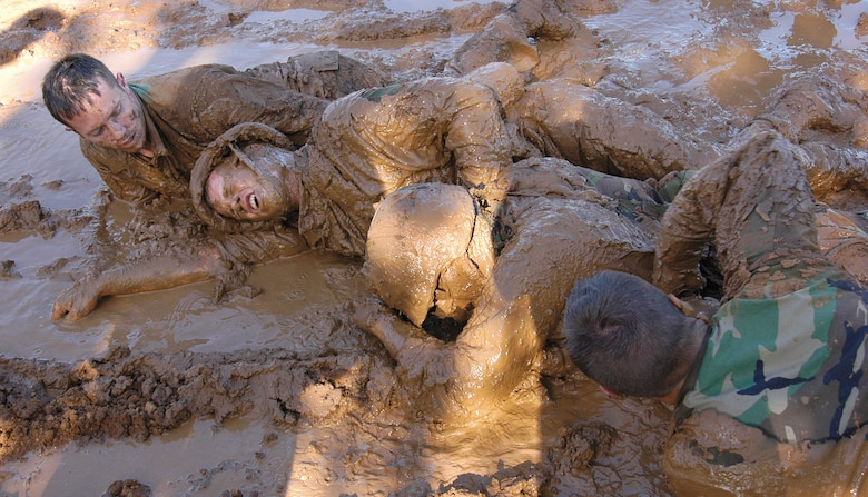 """Airmen strain to move inches through mud, perfecting low- and high-crawl techniques during week one of the Combat Readiness School at Tinker AFB, Okla.  Instructors drill into students the motto of """"no one left behind"""" and watch the concept take hold as Airmen enter the pit as individuals, but struggle to the end as a team, encouraging and pulling each other to the finish. Fire team members from left are; Staff Sgt. Rich Brumbaugh, 349th Communications Squadron, Travis AFB, Calif; Staff Sgt. Christopher Kelley, 33rd Combat Communications Squadron, Tinker; Senior Airman Raid Alawar, 349th CS; and Airman Micheal Garner, 31st CCS, Tinker. (Air Force photo by Margo Wright)"""