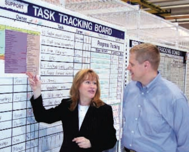 Teri Gary, Defense Supply Center Richmond's transformation liaison officer, and Shawn Tellers, Team Battelle supply chain management leader, review the F100 Engine Support Cell detailed cell design progress board to ensure supply chain management processes have been incorporated. Streamlined supply chain management ensures parts are located closer to the mechanic and are always available when needed. (Air Force photo by Paul Chalifoux)