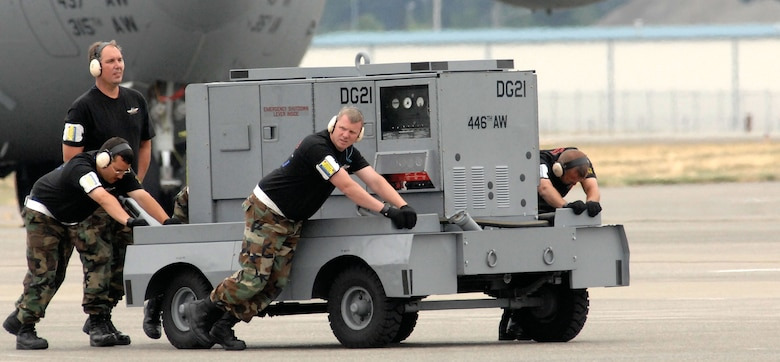 Members of the 446th Airlift Wing's Rodeo maintenance team, McChord Air Force Base, Wash.,  push a cart away from the C-17 during Rodeo 2007, held July 23-27 at McChord. (From left to right) Tech. Sgt. Michael Silva, Master Sgt. Michael Stewart, Tech. Sgt. Thomas Teal and Tech. Sgt. Thomas Timney. (U.S. Air Force photo/Abner Guzman)