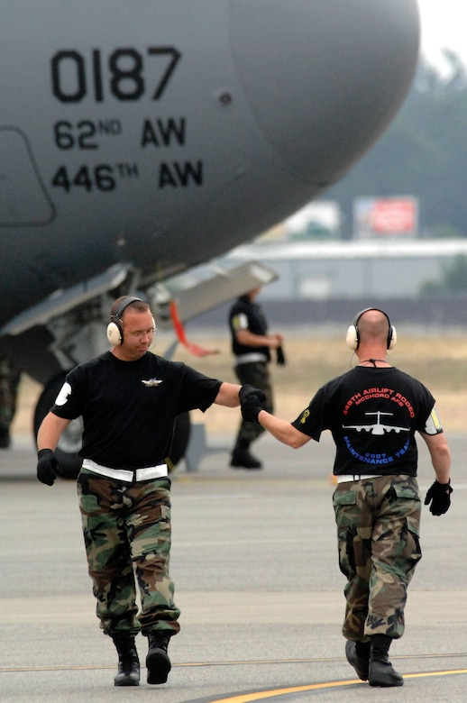 Reservists Tech. Sgt. Burke Stott, left, and Master. Sgt. Kevin Smith, 446th Airlift Wing maintenance team members from McChord Air Force Base, Wash., greet it other as they cross paths during Rodeo 2007, held July 23-27 at McChord. (U.S. Air Force photo/Abner Guzman)