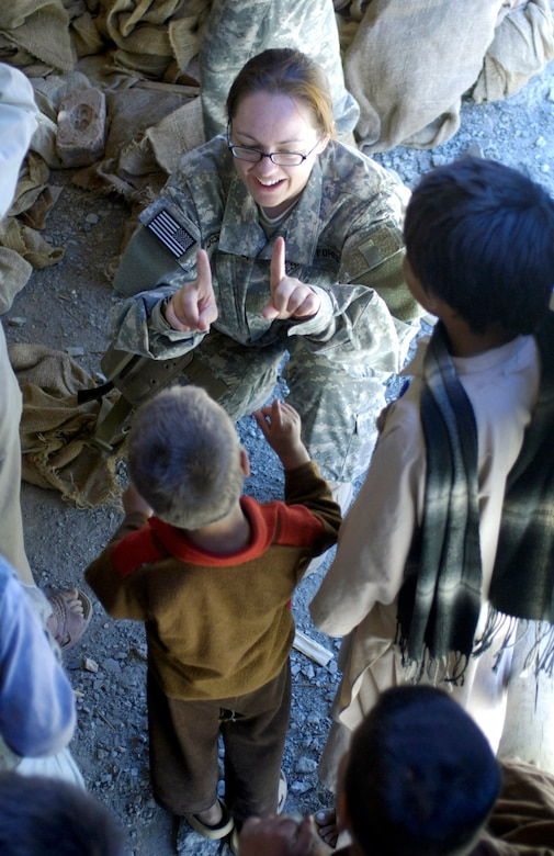 Staff Sgt. Julie Weckerlein plays a finger game with a local village boy at a school construction project Aug. 4 in the Paryan district of Panjshir Province, Afghanistan.  Sergeant Weckerlein is a print journalist deployed from the Pentagon and assigned to the U.S. Central Command Air Forces news team based in Southwest Asia. She is traveling with the Panjshir Provincial Reconstruction Team operating in Afghanistan. (U.S. Air Force photo/Master Sgt. Jim Varhegyi)