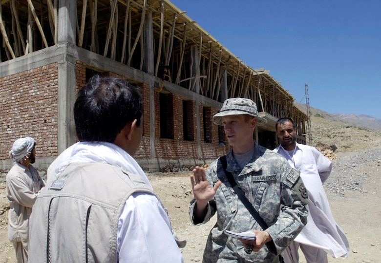 First Lt. Lee Turcotte discusses the progress of a school construction project with the contractor Aug. 4 in the Paryan district of Panjshir Province, Afghanistan.  Lieutenant Turcotte, a civil engineer from McGuire Air Force Base, N.J., is a member of the Panjshir Provincial Reconstruction Team. The school project is one of several being monitored by the PRT.  Once completed the school will accommodate children from several villages in the province. The children are currently attending classes in makeshift tents overlooking the construction site. (U.S. Air Force photo/Master Sgt. Jim Varhegyi)
