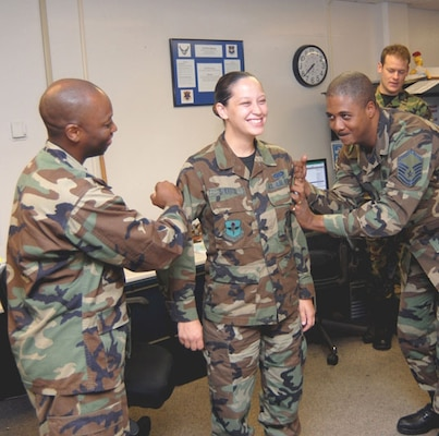 "Sr. Airman Jessica Sherrod (center) of the 12th Comptroller Squadron gets her staff sergeant rank ""pinned on"" by Maj. Kerry Britt (left) and Senior Master Sgt. Bryan Anderson Wednesday. Airman Sherrod celebrated her birthday the same day she received word of her promotion. (Photo by Melissa Peterson)"